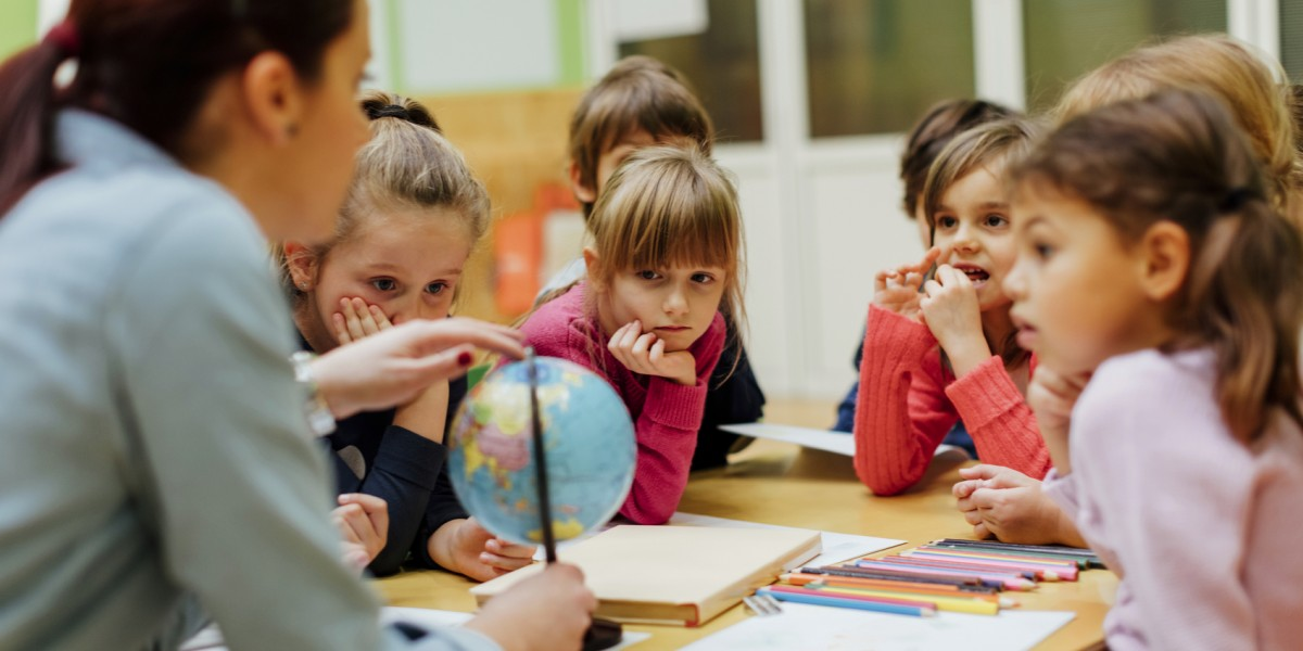 Preschool teacher and children using globe.