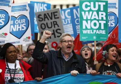 英國示威人士高舉「Cut War Not Welfare」的牌表達訴求。 圖片來源:路透社