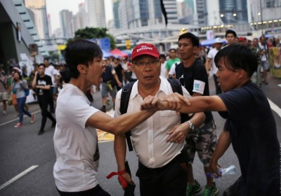 Pro-democracy protesters argue with a man (C) as he walks away from an area blocked by protesters outside the government headquarters office in Hong Kong