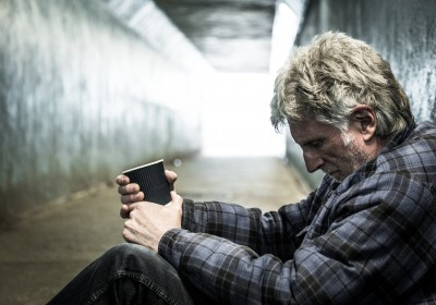 Homeless senior man alone in a subway tunnel. He is begging and holding out a paper cup in front of him and sitting on the floor with his knees drawn up into his body. The background is thrown out of focus but we can see the light at the end of the tunnel. Horizontal colour image with copy space.