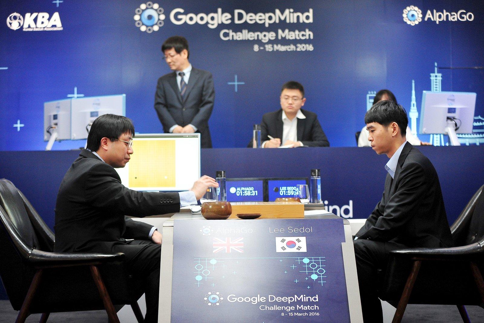 人工智能系統 AlphaGo 與棋手李世石首次對戰,研發團隊成員兼業餘棋手黃士傑(右)替 AlphaGo 走棋。 圖片來源:路透社
