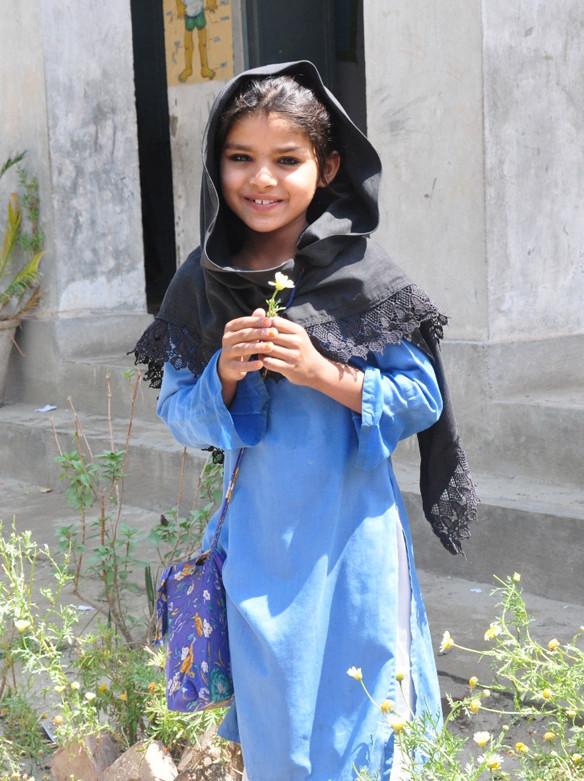 巴基斯坦七歲的塞瑪開心地穿著所住穆札法爾格爾縣村民捐贈的校服。