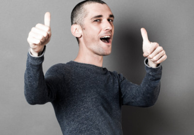 optimism concept - excited 30s man with short hair and thumbs up for congratulation or success, studio grey background, texture effects