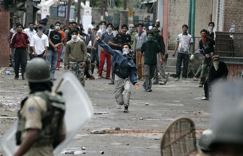 克什米爾示威者向印度警方扔石。 圖片來源:路透社