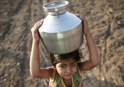 在烈日下,一位印度女孩頭頂滿載食水的鐵罐,走過 Latur 的田地,運水回家。(圖片來源:REUTERS)