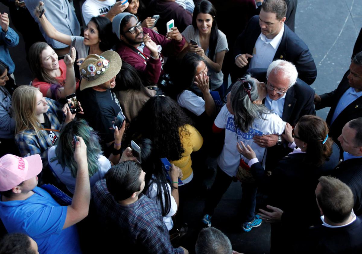 5 月 22 日加州爾灣美國大選集會外,支持者向民主黨候選人桑德斯獻吻。對手希拉莉離取得黨內提名僅數十票,選戰可謂塵埃落定。