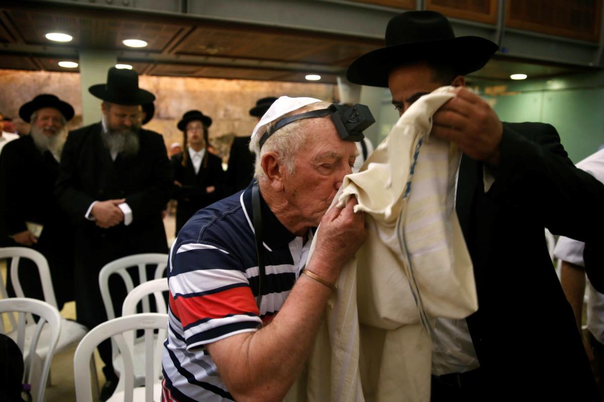 納粹集中營生還者 Ephraim Zevoltober 親吻一件猶太教禱告衣。5 月 2 日耶路撒冷舊城傳統猶太成人禮邀請 30 名種族滅絕倖存者出席,紀念屠猶死難者。