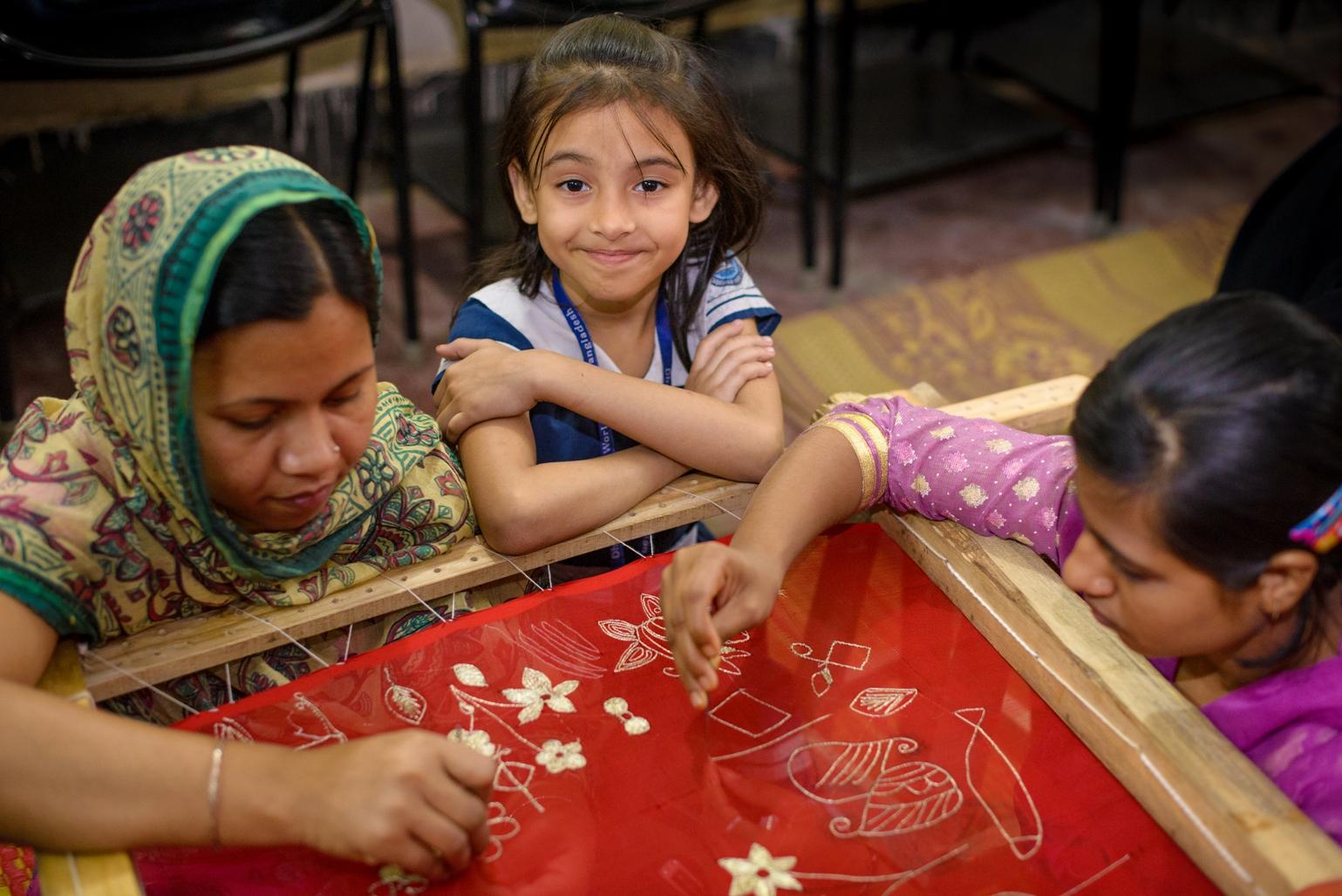 素美雅(中)和母親泰絲利瑪(左)在宣明會開設的社區中心學習孟加拉傳統刺繡技巧。