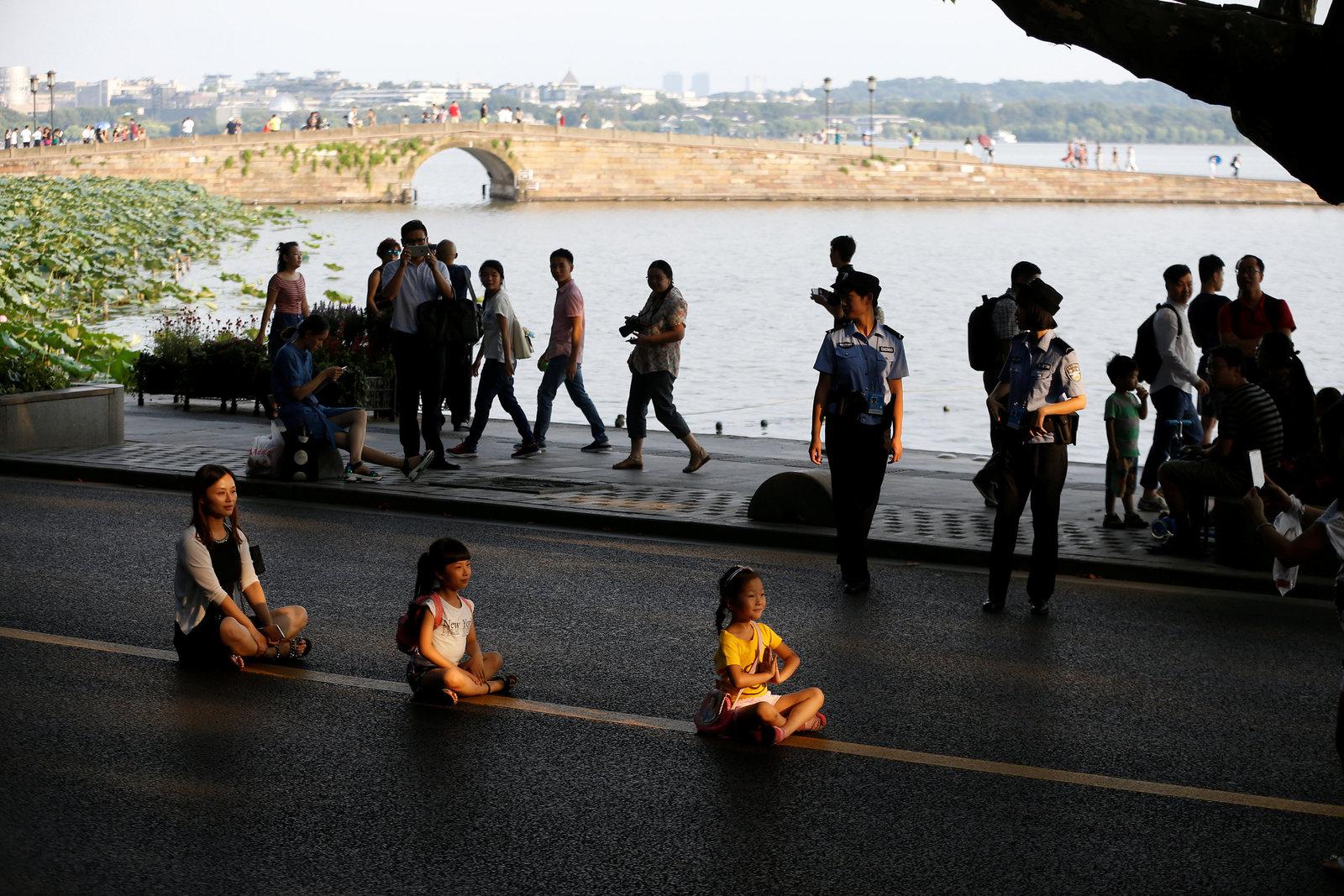 杭州多處封路後,走在馬路的公安,以及坐在馬路的遊人,都成為西湖「新景」。圖片來源:路透社