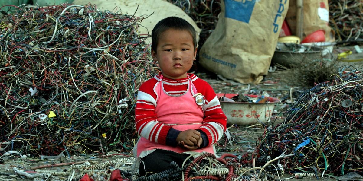 有拾荒兒童在被重金屬化學污染的電子垃圾場中尋有價值的零件。