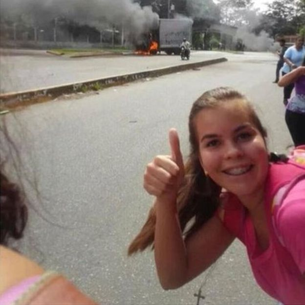 女孩在焚燒中的貨車前豎起拇指,表示一切情況良好。圖片來源:BBC