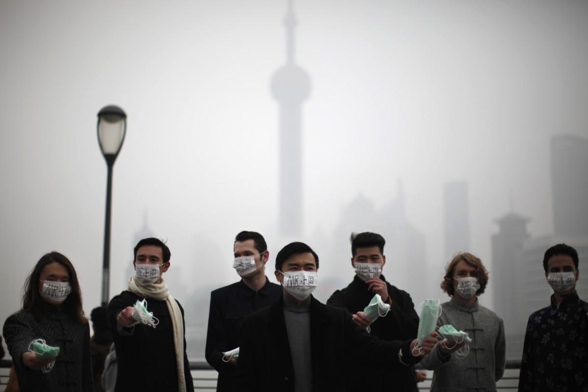 一班外國人在上海街上派發口罩。圖片來源:路透社