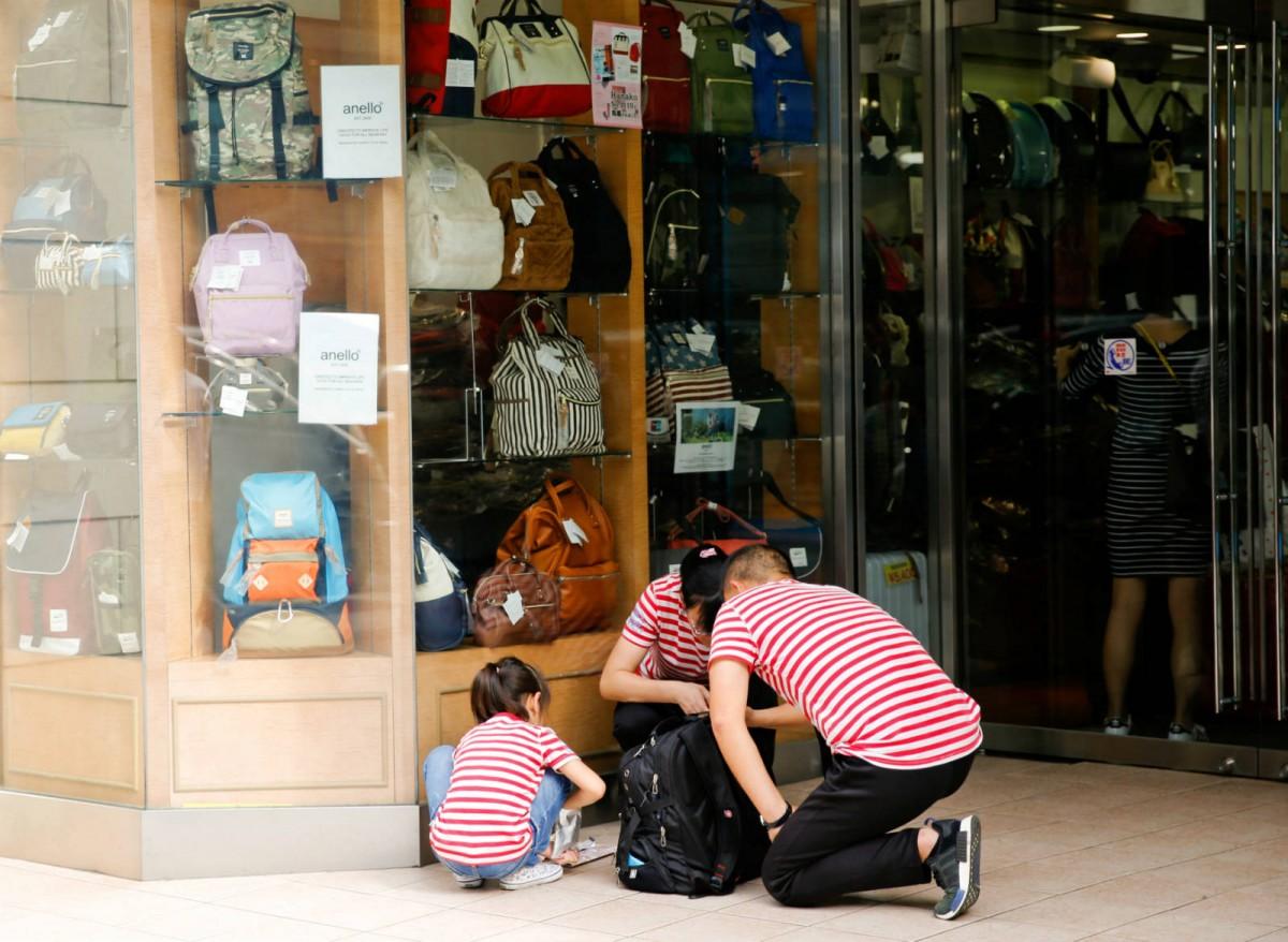 中國旅客在東京銀座商業區外整理行李。 圖片來源:路透社