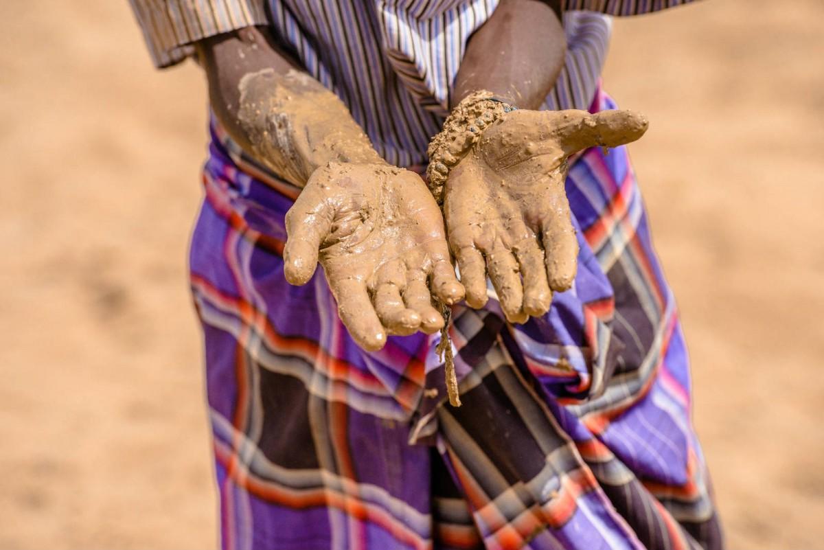 小孩子雙手沾滿了泥濘,證明了每一滴水都是得來不易。