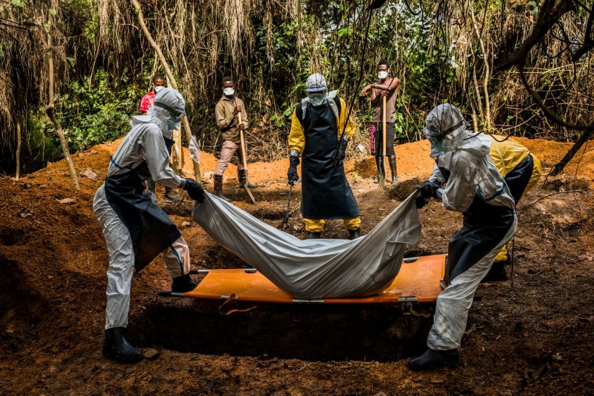 2014 年 10 月,利比里亞防疫人員正埋葬一名懷疑感染伊波拉病毒的死者。 圖片來源:紐約時報