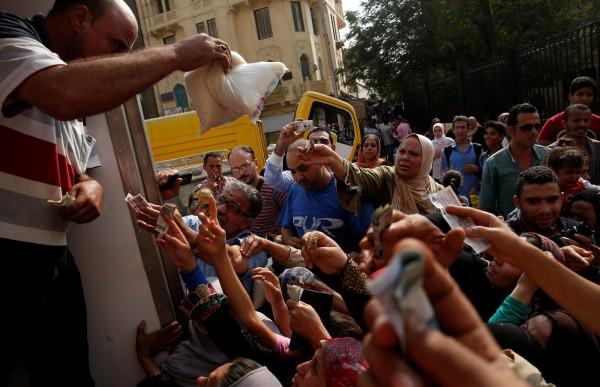 埃及人擠在貨櫃車前,搶購政府補品的糖。圖片來源:路透社