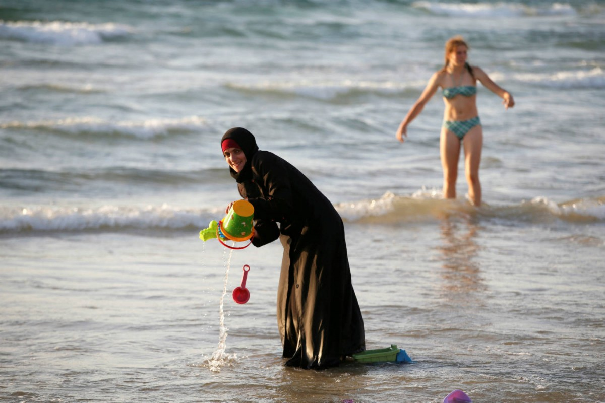8 月 21 日,特拉維夫的沙灘上,一名穿著頭巾和罩袍的穆斯林女人正在嬉水。