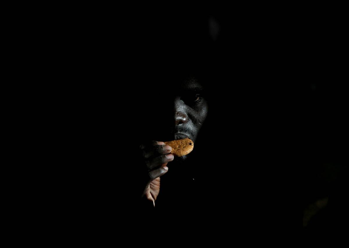 6 月 23 日,海上移民援助站的救援船上,一名剛被救起的利比亞移民正在吃餅乾。