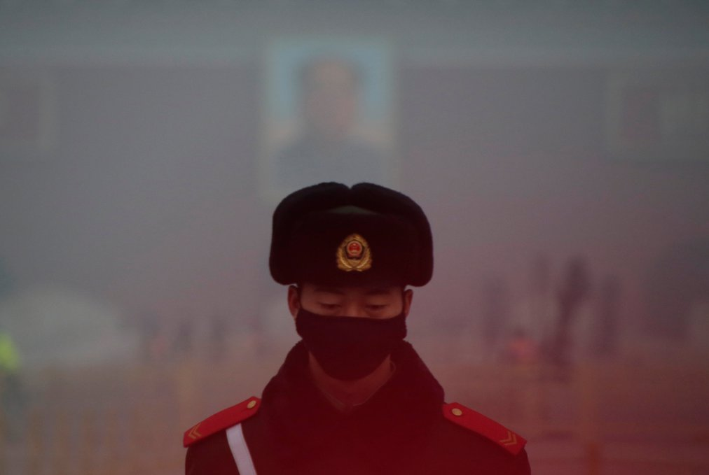 A paramilitary police officer wearing a mask stands guard