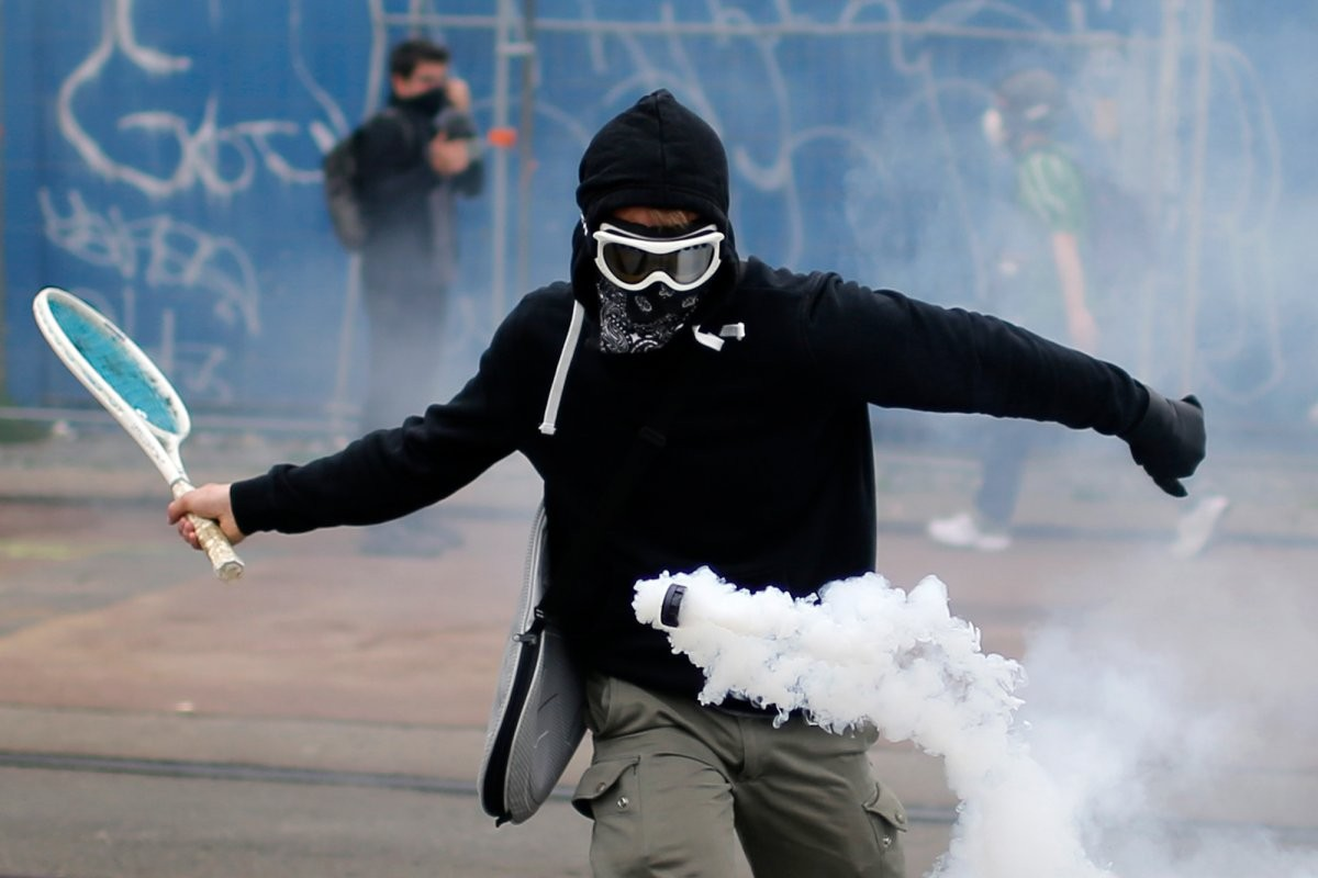 a-protestor-uses-a-tennis-racket-to-bounce-a-tear-gas-canister-during-a-demonstration