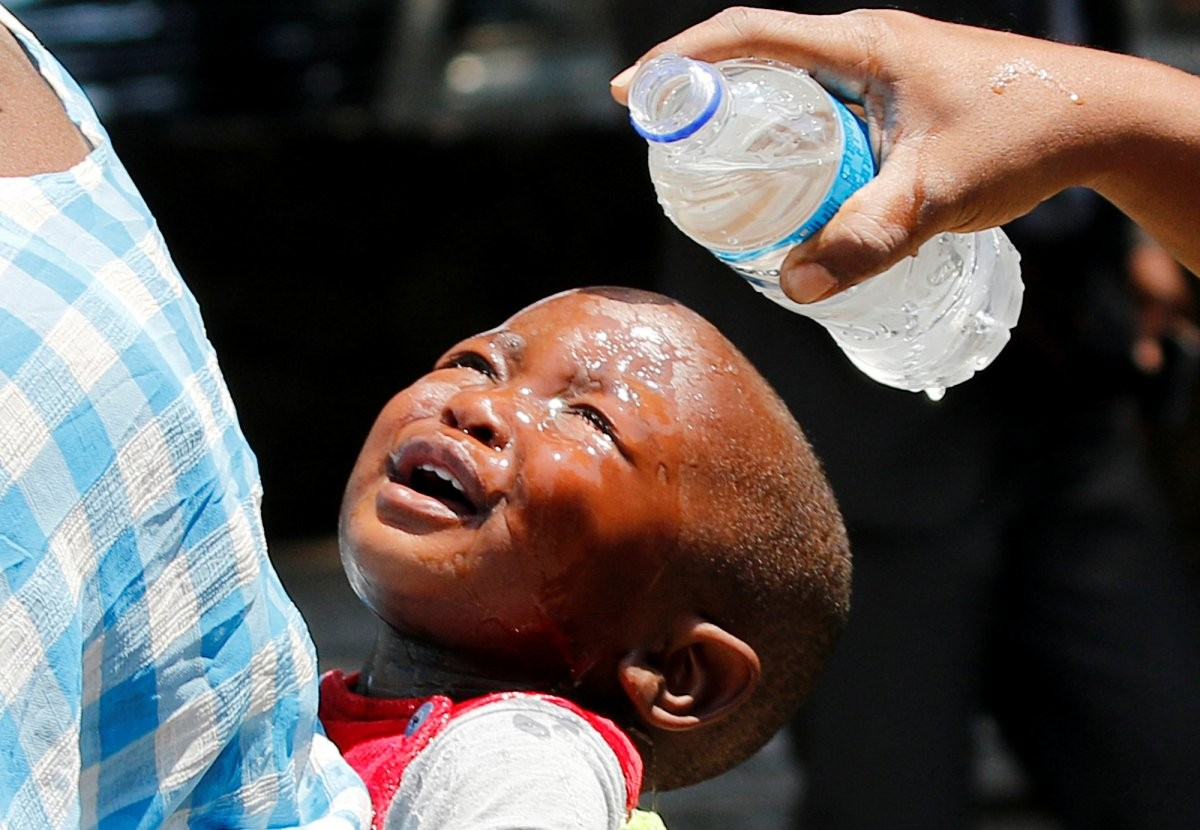 a-woman-pours-water-over-a-child-affected-by-teargas-after