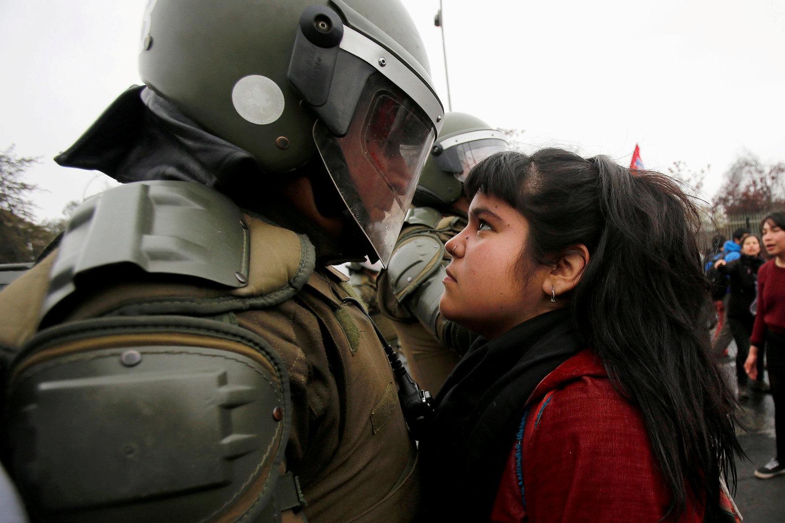 9 月 11 日,智利舉行軍事政變 43 週年紀念遊行,一名示威者緊盯著防暴警察。