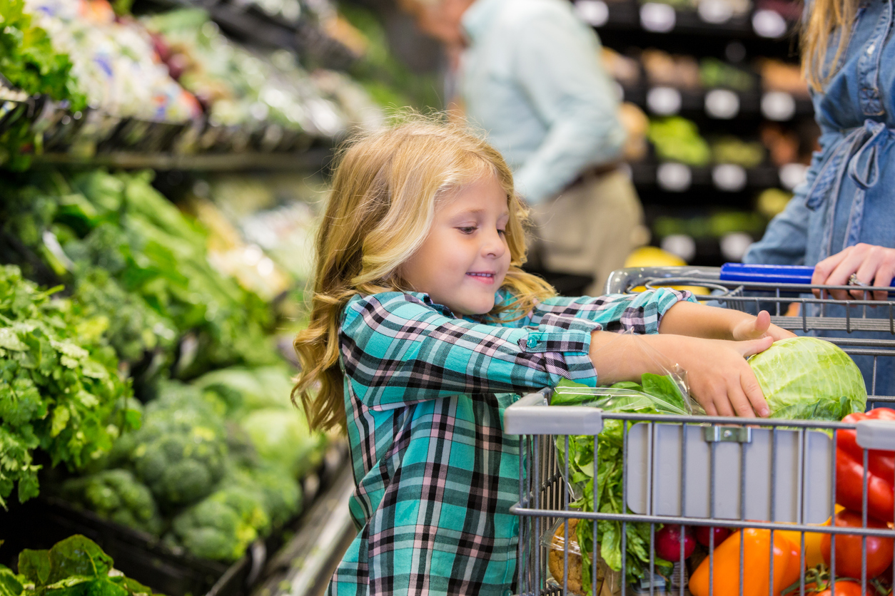 Elementary age Caucasian blonde little girl is smiling while placing lettuce in shopping cart. Child is shopping for produce and healthy food with her mother in local grocery store. Child is wearing a plaid shirt. Other customers are shopping in background.
