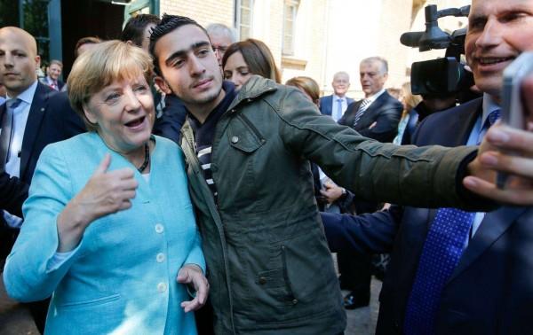 2015 年 9 月,一名移民與德國總理默克爾在柏林斯潘道一處難民營合照。 圖片來源:路透社